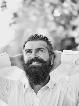 Handsome young stylish hipster man with smiling face and long beard in white shirt standing outdoor on natural background sunny day outdoor Stok Fotoğraf