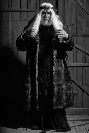 木製の背景に宝石石ジュエリーと深刻な顔と髪の毛皮のコートとクラウンに長いひげと古いドルイドを生やした