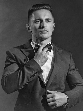 young handsome gentleman in fashion black suit white shirt and bow tie in studio Фото со стока