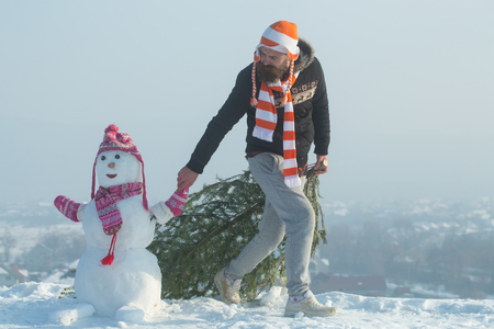Holiday celebration concept. Hipster dragging xmas tree on snowy winter road. Guy and snow sculpture wearing hats and scarves. Christmas and new year. Man and snowman walking on blue sky.