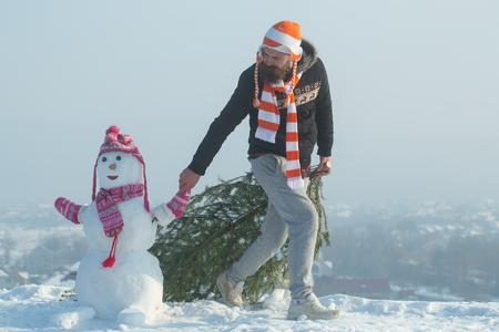 Vakantie feest concept. Hipster slepende Kerstmis boom op besneeuwde winter weg. Kerel en sneeuwbeeld die hoeden en sjaals dragen. Kerstmis en Nieuwjaar. Mens en sneeuwman die op blauwe hemel lopen. Stockfoto