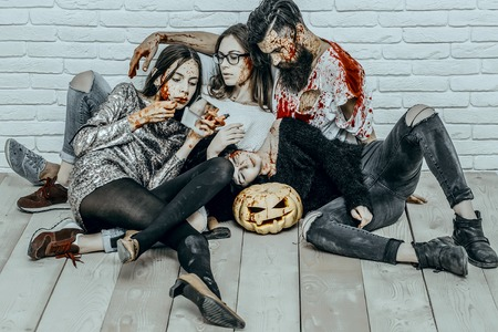 Halloween women with red blood splatters. Friends relaxing on wooden floor. Girl vampire applying lip gloss makeup. Bearded man with bloody pumpkin and axe. Halloween holiday celebration concept.