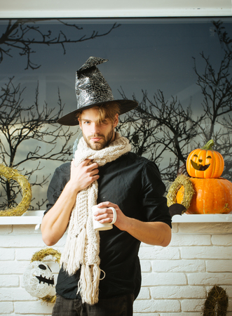 Halloween man holding cup at window with autumn trees. Macho wearing witch hat and scarf. Holiday symbols and decorations. Magic potion concept. Warm and homely atmosphere.