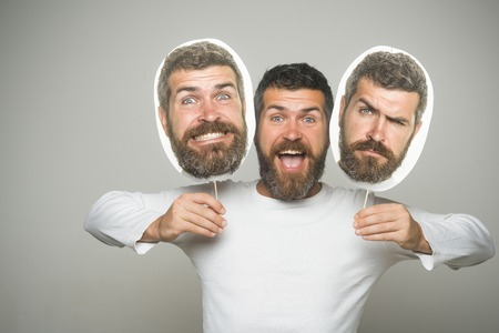 Man with long beard and mustache. Guy or bearded man on grey background. Feeling and emotions. Hipster with surprised and serious face hold portrait nameplate. Barber fashion and beauty.
