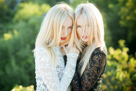Sisters twins posing on natural landscape. Beauty and fashion. Two women with red lips and long blond hair. Dualism and dualistic nature. Contrasts and opposites concept. Фото со стока
