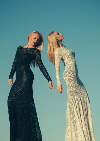 Women wearing black and white dresses. Opposites and contrasts concept. Fashion and beauty. Two girls with long blond hair posing on blue sky. Choice, decision and future. Фото со стока