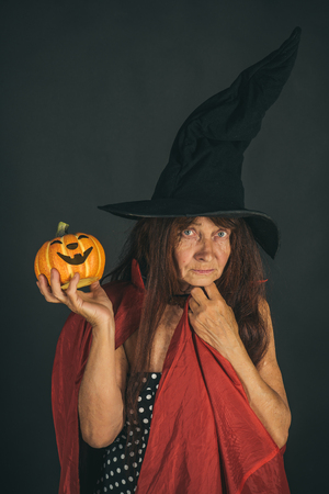 Halloween senior lady holding pumpkin on black background. Woman with long red hair in witch hat and coat. Evil spell and magic. Trick or treat. Holiday celebration concept.