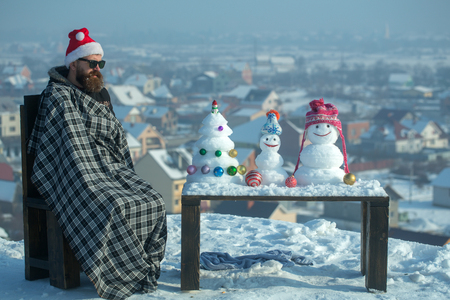 Man in plaid blanket sitting on chair on winter day. Hipster in red santa hat and glasses. Snowmen and snow xmas tree on wooden table. Christmas and new year. Holidays celebration concept Stock Photo