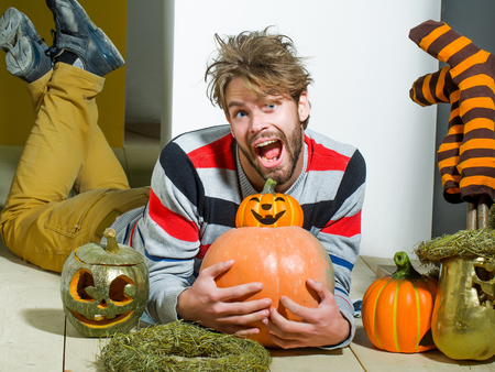 Halloween autumn and harvest season. Man with messy hair happy smiling on floor. Holidays celebration concept. Pumpkins, striped stockings and wreath. Trick or treat.