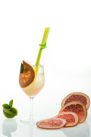 Drink and food. Party and summer vacation. Alcoholic beverage and orange at restaurant. Cocktail isolated on white background. Fruit slice of grapefruit in cocktail glass at bar.