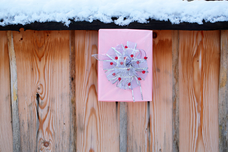 Christmas present on snowy fence on wooden background. Gift box of pink paper and bow with red berries. Winter palisade with white snow. xmas and new year. Holidays celebration concept.