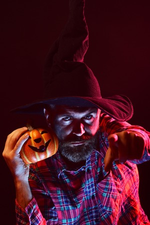 Halloween magic illumination and jack o lantern. Sorcerer with beard pointing finger in red light. Autumn holiday celebration. Mystery and nightmare concept. Man in witch hat holding pumpkin in dark.