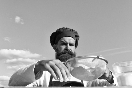Man cook chef with beard on handsome face in white and red uniform cooking dough with strainer sunny outdoor on blue sky background Stock fotó