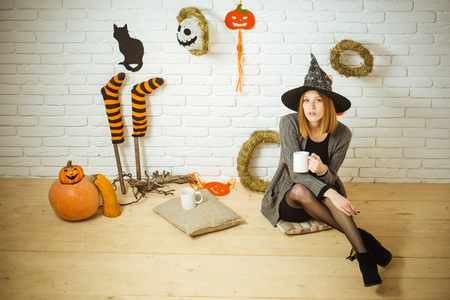 Halloween coffee or tea break. Woman in witch hat with cups. Girl sitting on wooden floor. Holiday celebration concept. Pumpkins, stockings, black cat, wreaths, mummy decorations on brick wall.