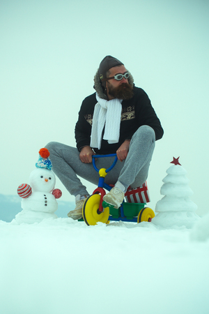Hipster riding tricycle on snowy landscape. Man in pilot glasses and hat on bike. Snowman and snow xmas tree on winter day. Holiday celebration concept. Christmas and new year fun. Stock Photo
