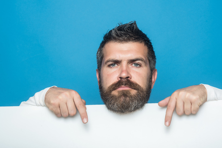 Man with long beard and mustache. Guy or bearded man on blue background. Barber fashion and beauty marketing. Hipster with serious face hold paper. Feeling and emotions.