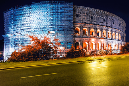 Colosseum with scaffolding under restoration at night Rome, Italy. Roman amphitheatre with light illumination on dark sky. Renovation, repairing, retouching concept. Landmarks and architecture.