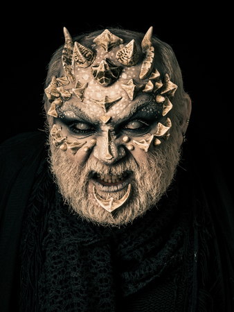 Monster with thorns and horns. Evil face with dragon skin and grey beard. Man angry with blind eyes. Demon baring teeth on black background. Horror and fantasy concept.