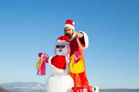Santa man with pointing finger hand. Snowman in pink wig, glasses, hat with shopping bags. Hipster in red costume on blue sky. Christmas and new year presents. Winter holidays concept, copy space