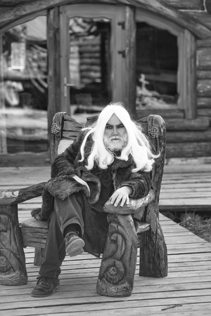 Old bearded man wizard with long white hair and beard in fur coat sits in wooden chair on log house background Reklamní fotografie
