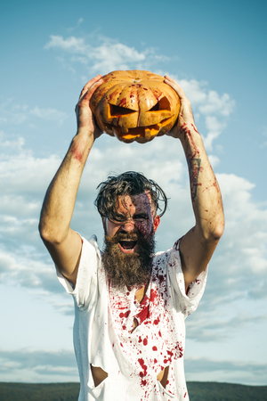 Halloween man holding pumpkin overhead on cloudy blue sky. Hipster with red blood shouting angry. Soldier in bloody torn tshirt with jack o lantern. Aggression, war concept. Autumn holiday celebration