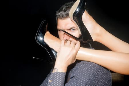 Romantiek en verliefd. Benen van vrouw in schoenen bij de mens met baard. Jongen aan tafel met vrouwelijke benen. Liefde en relaties, domineren. Mens in overhemd op zwarte achtergrond wordt geïsoleerd die. Stockfoto