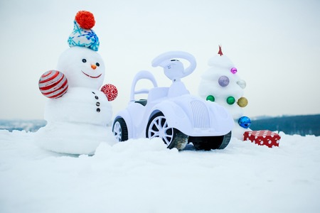 smiley face car: Snowman and toy car on snowy background. Snow sculpture with smiley face on winter day. Christmas tree and present box on white sky. xmas and new year. Holidays celebration concept.