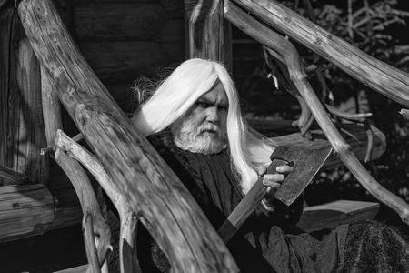 長い銀色の髪の毛にひげと古い男ドルイド コート屋外の木造背景晴れた日に大きな鋭い斧を保持しています。 写真素材