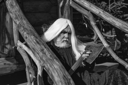 Old man druid with long silver hair and beard in fur coat holding big sharp axe on wooden house background sunny day outdoor