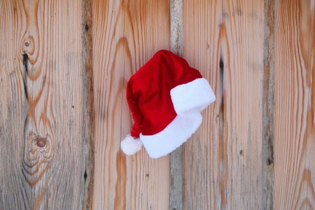 Santa claus hat on fence. Red santa cap on wooden background. Palisade planks with timber texture. Christmas and new year. Holidays celebration concept. Stock Photo