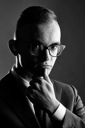 young fashion businessman with nerd glasses on thoughtful face and stylish hairdo in jacket with tie on studio background Stock Photo