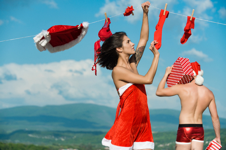 Xmas red costume on rope with pin. Laundry and dry cleaning. New year guy with muscular body on blue sky. Couple in love of man and girl hanging clothes for drying. Christmas man and woman family. Stock Photo