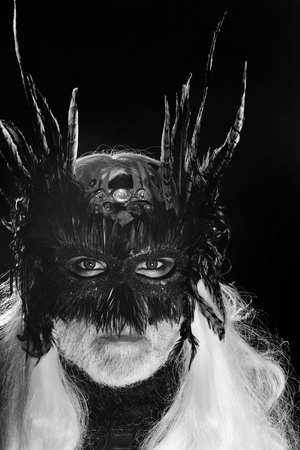 Male bearded face with long white hair and ominous sight in vintage decorative masque with dark brown feathers for fancy ball on black background studio Stock Photo