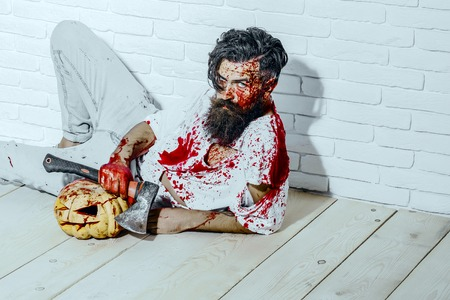 Halloween psychopath bleeding in torn tshirt. Man lying with axe and pumpkin on wooden floor. Halloween holiday concept. Bearded hipster with red blood splatters. Maniac and bloody jack o lantern.