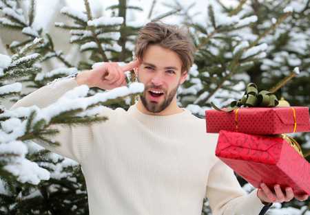 Macho pointing finger with presents on winter day. Man holding red boxes in snow wood. Season greetings and xmas gifts. Merry Christmas and happy new year. Holidays celebration concept.