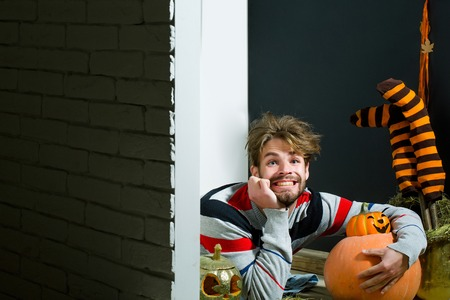 Halloween holidays celebration concept. Man with messy hair happy smiling on floor. Autumn and harvest season. Pumpkins, striped stockings and wreath. Trick or treat, copy space Stock Photo