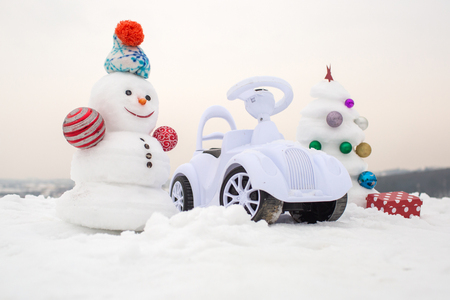 smiley face car: Snow sculpture with smiley face on winter day. xmas and new year. Christmas tree and present box on white sky. Holidays celebration concept. Snowman and toy car on snowy background.