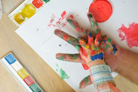 Care, love or adoption concept. Hands in colorful paints and multicolor palette on white paper. Fathers day and family. Arts and handprint painting. Support and protection.