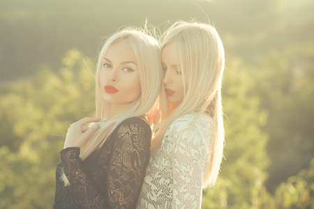 Sisters twins posing on sunny natural landscape. Two women with red lips and long blond hair. Contrasts and opposites concept. Dualism and dualistic nature. Beauty and fashion.