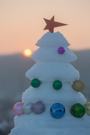 Snow sculpture with red star on natural background. xmas and new year celebration. Decorations and ornaments. Winter holidays concept. Christmas tree with baubles on sunset sky.