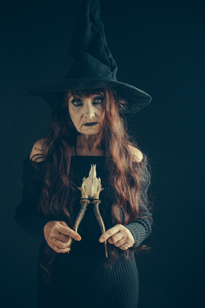 Halloween old lady in witch hat. Halloween old woman on black background. woman in black with long red hair and makeup. holiday celebration. traditional party.