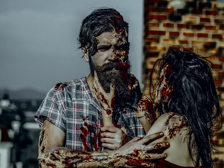 Halloween girl with bloody brunette hair. Horror and violence. Holiday celebration concept. Woman strangling man with bloody hands. Vampire with beard and red blood wounds outdoors.