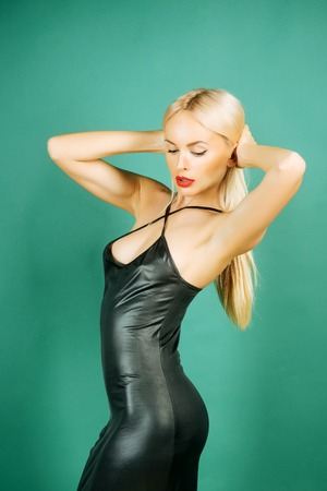 Glamour lifestyle concept. Fashion and beauty. Woman posing in black latex dress. Erotic and seduction. Girl with long blond hair on green background.