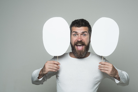man with long beard on happy face with paper nameplate on grey background, copy space Foto de archivo
