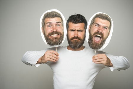 Guy or bearded man on grey background. Hipster with serious, angry and scary face hold portrait nameplate. Barber fashion and beauty. Feeling and emotions. Man with long beard and mustache.