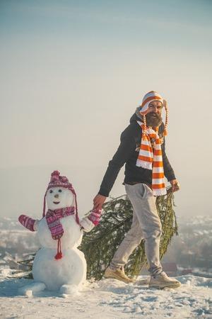 Kerstmis en Nieuwjaar. Mens en sneeuwman die op blauwe hemel lopen. Kerel en sneeuwbeeld die hoeden en sjaals dragen. Hipster slepende Kerstmisboom op sneeuw de winterweg. Vakantie feest concept.