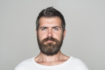 Hipster with serious face. Guy or bearded man on grey background. Barber fashion and beauty. Feeling and emotions. Man with long beard and mustache. Banco de Imagens