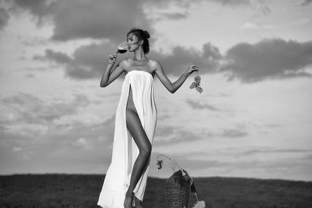꽤 젊은 여자 또는 여자가 백인 섹시 드레스 denewed 유리 위커 병 포도 나무 및 포도 푸른 하늘 통해 자연에 레드 와인