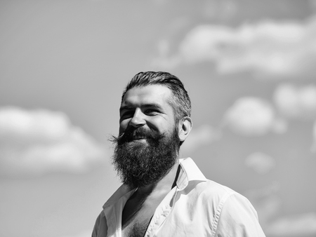 Handsome young stylish hipster man with long beard in white shirt standing outdoor on blue sky background sunny day outdoor