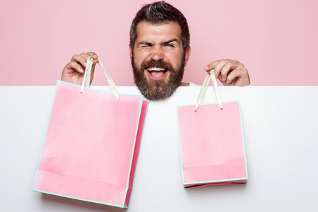 Man with long beard with pink shopping bag. Christmas and birthday. Guy with happy face and gift pack. Hipster with present package on pink background. Holiday celebration and black friday shopping.